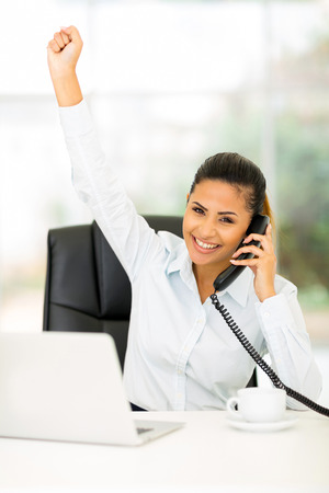 excited businesswoman hearing good news on the phone photo