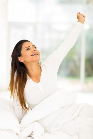 levantandose: mujer joven de levantarse por la mañana y se extiende Foto de archivo
