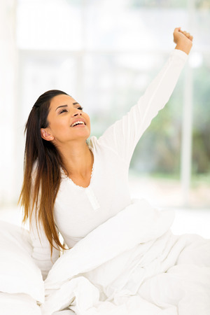young woman getting up in the morning and stretching photo