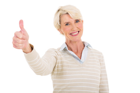 thumbs up woman: cheerful mature woman giving thumb up isolated on white Stock Photo