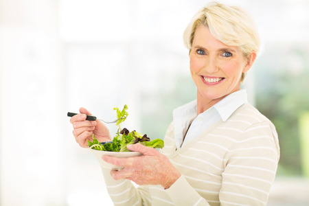 cheerful mature woman having green salad photo