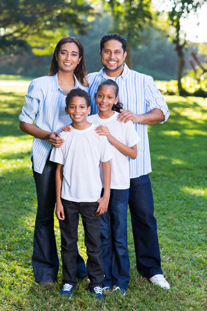 young indian family standing together outdoors photo