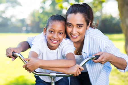cute indian mother and her daughter outdoors in park on a bike photo