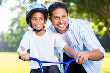 cheerful indian man helping his son to ride a bike in forest photo