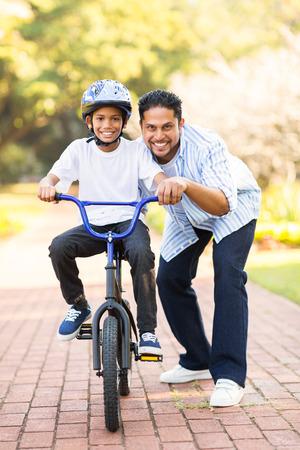 행복한 작은 인도 소년 그의 아버지의 도움으로 자전거를 타고 학습