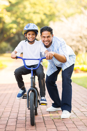 teach: happy little indian boy learning to ride a bike with help of his father
