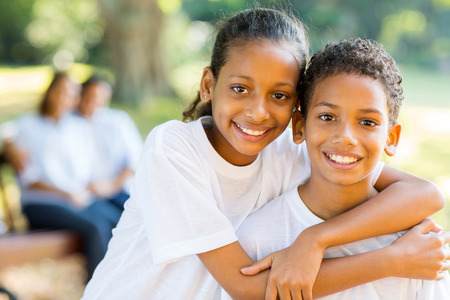 girl looking up: cheerful little indian sister and brother standing in front of parents in the park Stock Photo