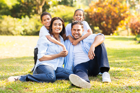 happy indian family sitting on grass in the park