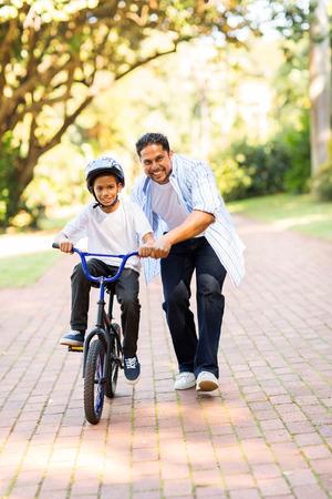 jugando: feliz padre indio ense�ando a su hijo a andar en bicicleta en el parque Foto de archivo