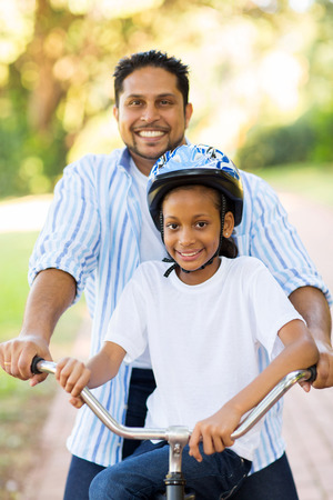 indian summer: happy indian father and daughter outdoors on a bike Stock Photo