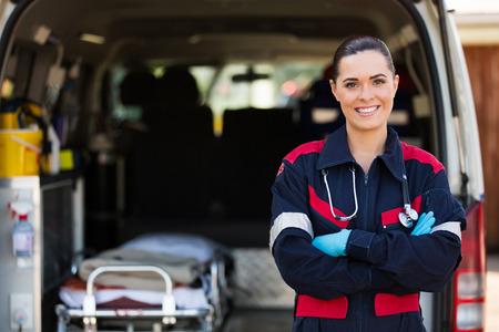 atractiva joven trabajador de servicio médico de emergencia femenino delante de la ambulancia