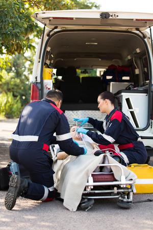 Paramedic putting oxygen mask on unconscious patient
