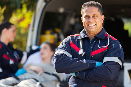 handsome paramedic in front of patient and colleague