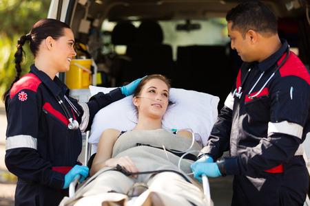 paramedic: amigable paciente joven reconfortante paramédico antes de transportarlo al hospital