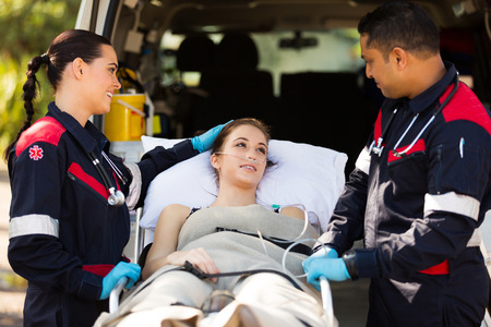 friendly zdravotník uklidňující mladého pacienta před transportem ji do nemocnice Reklamní fotografie