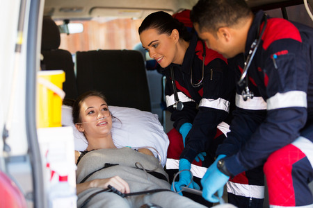 emt: friendly paramedic team talking to patient in ambulance