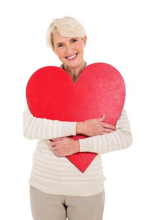 modern love: beautiful mid  age woman hugging red heart shape