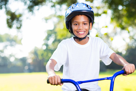 happy young indian boy riding a bike outdoors photo
