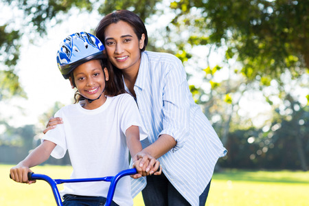 beautiful indian mother teaching her daughter to ride a bike at the park photo