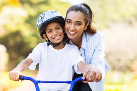 vrolijke Indiase moeder die haar zoon onderwijst om een fiets te rijden Stockfoto