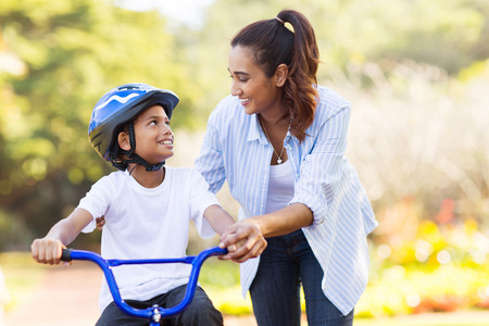 indian summer: loving mother help her cute son ride a bicycle Stock Photo