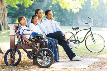 modern indian family sitting on bench and relaxing in the park photo