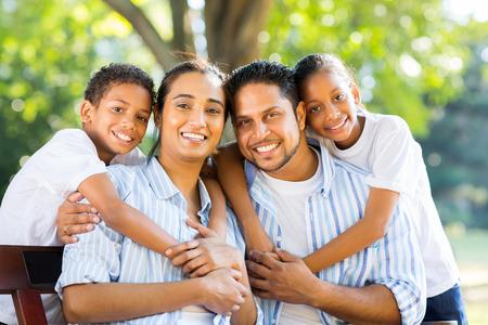 공원에서 함께 앉아 쾌활한 젊은 인도 가족