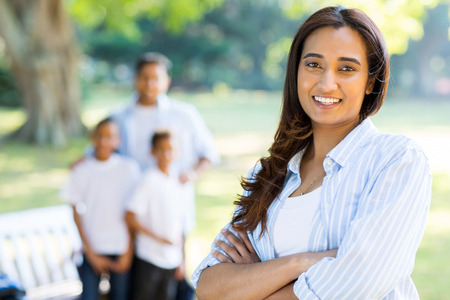 indian happy family: gorgeous indian woman standing in front of family outdoors Stock Photo