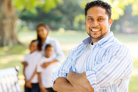 good looking young indian man standing in front of family outdoors photo