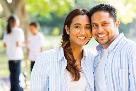 ni�os felices: feliz pareja india de pie delante de los ni�os al aire libre Foto de archivo