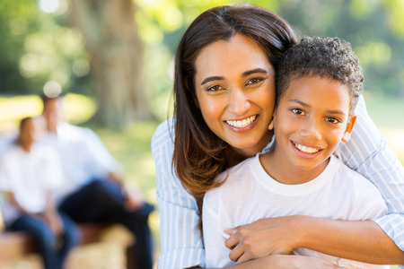 happy indian mother hugging her son in front of family outdoors photo
