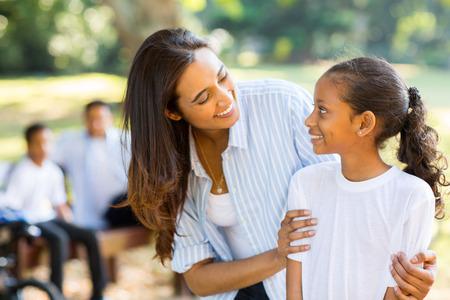 padres hablando con hijos: feliz madre e hija indio lindo delante de la familia Foto de archivo