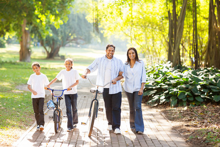 happy indian family of four walking outdoors in the park Stock Photo
