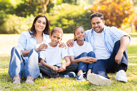 four person: cheerful indian family sitting together outdoors