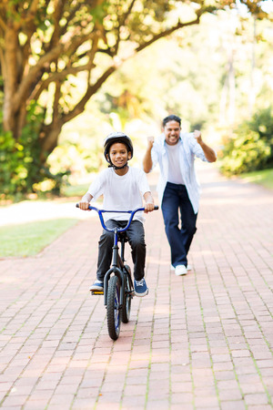 happy father cheering when his son can ride a bike on his own for the first time photo