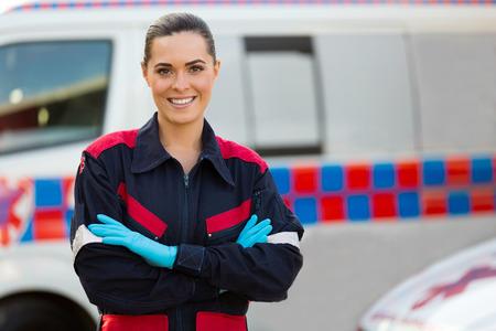 schöne weibliche Sanitäter mit den Armen vor der Ambulanz überquerte Standard-Bild
