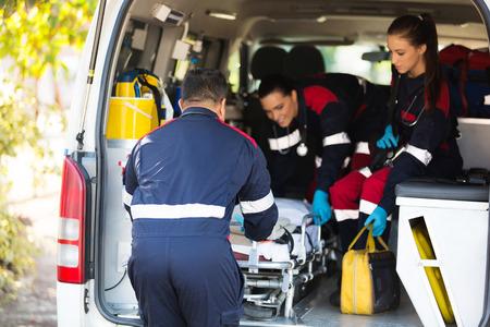 equipe ambulância puxando uma maca para fora do veículo Imagens