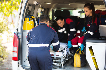 equipo de la ambulancia que tira de una camilla de vehículo Foto de archivo
