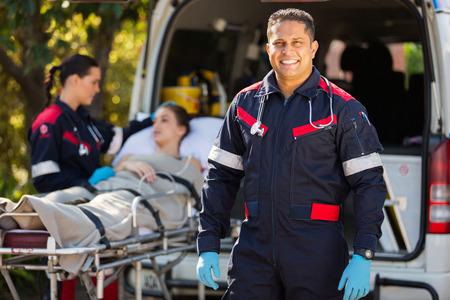 paramédico guapo con su colega y paciente en el fondo