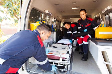 チーム救急隊員救急車から担架を取って
