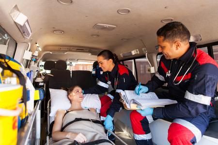 Pflege Sanitäter im Gespräch mit auf Krankenwagen auf dem Weg ins Krankenhaus Patient Standard-Bild