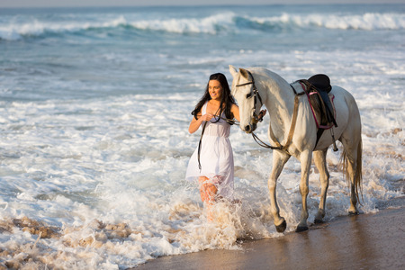 happy young woman walking with a white horse on beach photo