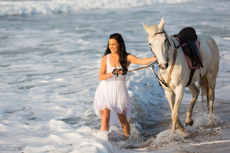 sea mammal: smiling young woman walking with a white horse on beach