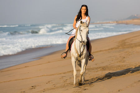 beautiful young woman riding a horse on beach in early morning photo
