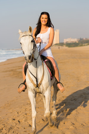 happy young woman riding a horse on beach in the morning  photo