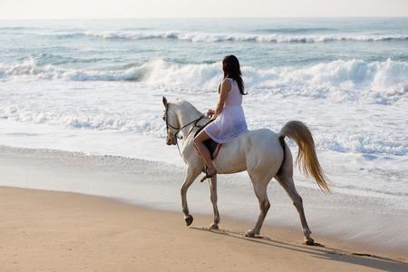 girl in white dress enjoying horse ride on the beach photo
