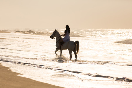 young woman horse ride in the water on beach photo