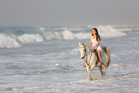 beautiful young woman riding horse on beach photo