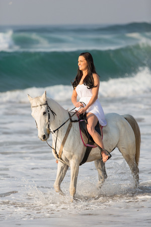gorgeous woman horse ride in the water on beach photo