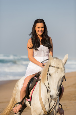 young beautiful woman on the horse by the beach photo